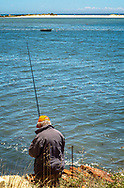 A fisherman on the rocks in Fabrica, Portugal on a sunny day in June.