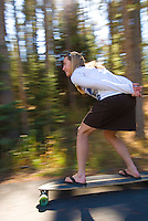 A young woman rides a skateboard in Jackson Hole, Wyoming.