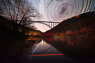 The stars whirl around Polaris above the New River Gorge Bridge of West Virginia, reflecting light trails in the river showing the Earth's rotation over 4 hours.