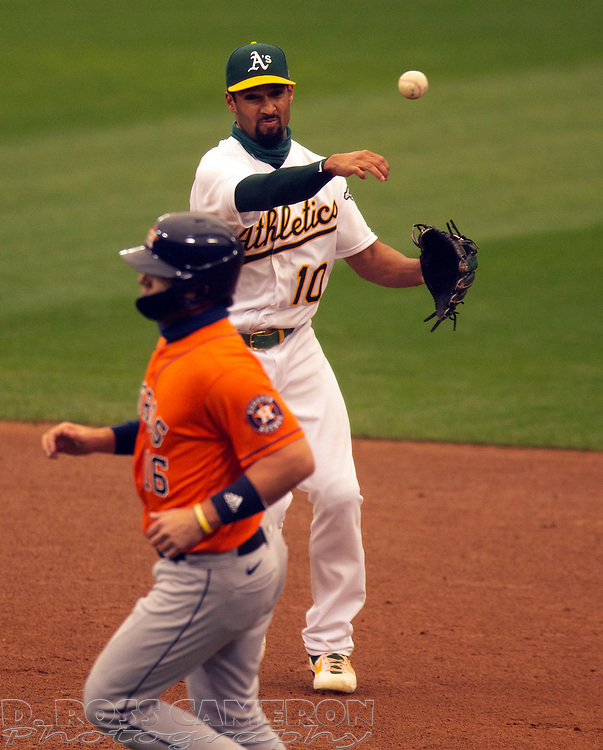 Sep 10, 2020; Oakland, California, USA; Oakland Athletics shortstop Marcus Semien (10) throws past Houston Astros Aledmys Díaz (16) to complete a double play during the sixth inning of a baseball game at Oakland Coliseum. Martín Maldonado (15) was out at first, but Josh Reddick (22) scored from third on the play. Mandatory Credit: D. Ross Cameron-USA TODAY Sports
