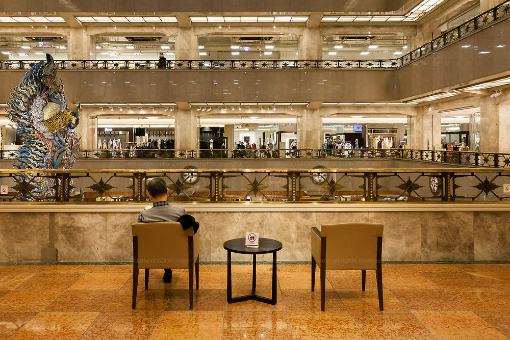A man sits reading a book, in the central areas of historic Mitsukoshi Department Store in Nihonbashi. Tokyo, Japan. Wednesday February 17th 2021