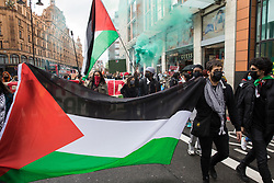 London, UK. 15th May, 2021. Activists walk with a Palestinian flag as hundreds of people take part in a Free Palestine SOS Colombia solidarity rally and march from the Colombian embassy to the Israeli Embassy. Speakers highlighted human rights abuses such as forced displacement being directed against Palestinians in Israel and the Occupied Territories and the killing, repression, detention and torture of peaceful demonstrators and human rights defenders in Colombia.