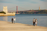 Two couples walking at the boardwalk near Tagus riverside seen from Champalimaud Center for the Unknown, with Belém tower on the left, 25th of April bridge in the center and Cristo-Rei (King Christ) on the right side.
