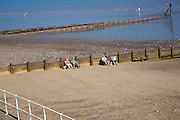 People sitting on sandy beach by wooden groynes, Hornsea, Yorkshire, England