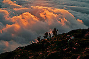 Hikers climbing Pico mountain after watching the sunset on the hill. Pico is the highest portuguese mountain with 2351m high