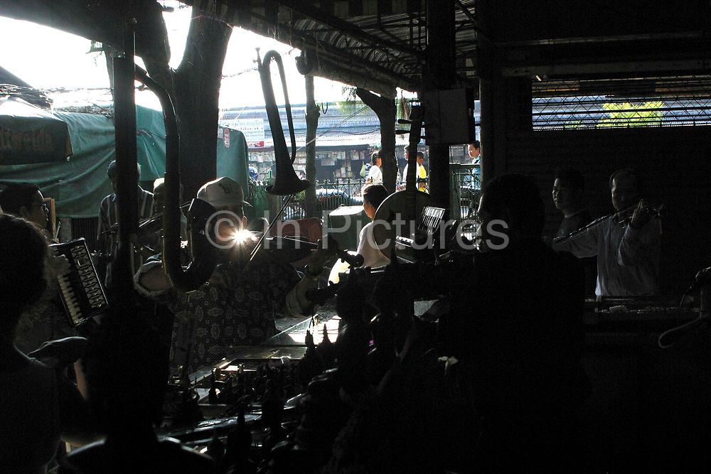 Locals play instruments including the violin at a music stand in the weekend market. Bangkok, Thailand.