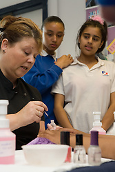 Beauty Therapist teacher demonstrating how to do a manicure to students,