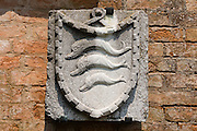 An old stone is carved with dolphins on a shield, on Torcello island, in the Venice Lagoon, Italy, Europe. Italy's Veneto region is named for the ancient Veneti people from the 900s BC. More than 100 small islands spread across the marshy Venetian Lagoon along the Adriatic Sea in northeast Italy, between the mouths of the Po and Piave Rivers. Barbarian invasions, such as Huns in 452 AD, drove mainland Veniti people to settle the islands. The population of Torcello peaked in the 900s AD with more people than the city of Venice. The Republic of Venice was a major maritime power during the Middle Ages and Renaissance, a staging area for the Crusades, and a major center of art and commerce (silk, grain and spice trade) from the 1200s to 1600s. The wealthy legacy of Venice stands today in a rich architecture combining Gothic, Byzantine, and Arab styles.