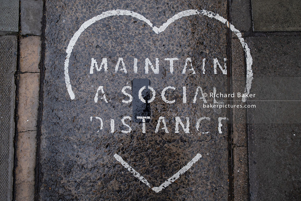 After being walked on for many months, a detail of fading stencilling asking passing pedestrians to maintain a social distance during the Coronavirus pandemic, on 24th September, in Soho, London, England. New restrictions are being re-introduced by the government after a sudden climb in the Covid infection rate, a predicted 'second spike'.