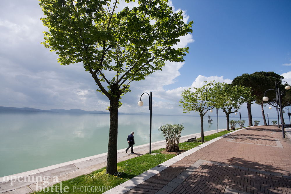 A man walks the shore of Lake Trasimeno in the town of Passignano sul Trasimeno, Umbria, Italy.