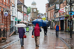 Chesham, UK. 18th June, 2021. Shoppers in Chesham High Street carry umbrellas in heavy rain on the day on which it was announced that the Liberal Democrats had won the Chesham and Amersham by-election. The Liberal Democrat candidate Sarah Green won by 8,028 votes from the Conservatives, overturning a 16,000 majority in a seat which had always previously returned a Conservative MP.