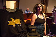 Flushing, NY - February 25, 2017. T-shirts and caps with the logo of Raven & Boar, a Hudson Valley farm and charcuterie featuring heritage pigs at the 2017 Charcuterie Masters at Flushing Town Hall. Ruby Metzner, one of the owners, and designer behind HiveMind Design, stands behind the merch.