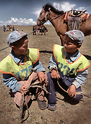 Two young twin contestants at a Nadaam horserace (about 20 Km speed race). Youngest racer are between 5 and 7 years old.<br /> Winning a race is quite the feat—prizes for winners include horses, and sometimes cars.<br /> Near Moron town, Khövsgöl province.