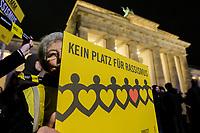 """20 FEB 2020, BERLIN/GERMANY:<br /> Eine aeltere Frau steht mit einem Schild """"Kein Platz für Rassismus"""" waehrend einer Gedenkveranstaltung für die Opfer des Anschlags in Hanau vor dem Brandenburger Tor<br /> IMAGE: 20200220-02-021<br /> KEYWORDS: Gedenken, Terror, Anschlag, Mahnwache, Demo, Demonstration, Versammlung"""