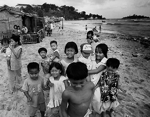 Kids live and play on the beach around Nha Trang harbour, Vietnam.
