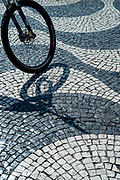 Cyclist wheel with spokes crossing paviers of wavy lines and geometric patterns in Rossio Square in Lisbon, Portugal