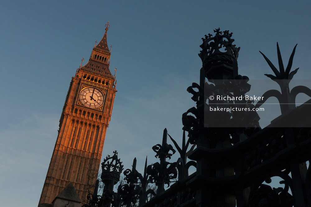 Silhouetted security railings featuring spikes and crowns and Elizabeth Tower of the British parliament, on 17th January 2017, in London England. The Elizabeth Tower (previously called the Clock Tower) named in tribute to Queen Elizabeth II in her Diamond Jubilee year – was raised as a part of Charles Barry's design for a new palace, after the old Palace of Westminster was largely destroyed by fire on the night of 16 October 1834. The new Parliament was built in a Neo-gothic style, completed in 1858 and is one of the most prominent symbols of both London and England.