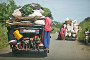 """Women and children ride in the trunk of a """"bush taxi"""" on the highway that runs between Bangui and Boali. A popular Nissan Sunny model, roughly modified to hold extra weight, these bush taxis charge 1,500 CFA (about three USD) to customers who travel one way from Bangui to Boali. These bush taxis, along with pick-up trucks and big lorries, are considered public transportation, and are usually overloaded with luggage and people, causing frequent breakdowns, flat tires, and accidents."""