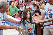 A young girl covered in sticky grits is weighed during the World Grits Festival rolling in the grits contest April 12, 2014 in St. George, South Carolina. Contestants have to roll in a vat of grits and the one with the most grits sticking to their body wins. Grits are a tradition Southern dish of thick maize-based porridge made from dried corn hominy.