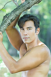 portrait of a handsome shirtless Asian American man outside