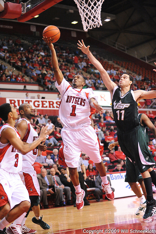 Mar 7, 2009; Piscataway, NJ, USA; Rutgers guard Corey Chandler (1) puts up a layup under the block attempt by South Florida center Alex Rivas Sanchez (11) during the second half of Rutgers' senior day game against South Florida at the Louis Brown Athletic Center.  Rutgers won 45-42.