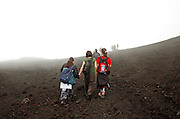 Hikers near the Smoke and steam emitted from Torre di Filosofo at 2920 meters, erupted 2003, on the Southern slopes of Mount Etna, The highest and most active volcano in Europe, Nicolosi, Sicily, Italy July 2006