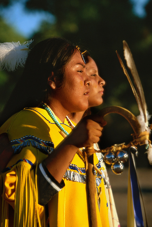 An Apache girl and her helper, both dressed in buckskin clothes, dance at the girl's Sunrise Dance, a first menstruation rite, on the San Carlos Apache Reservation, Arizona, USA. The girl holds a cane that symbolises longevity. The Sunrise Dance is supposed to prepare the girl for adulthood and to give her a long and healthy life without material wants.The ceremony is also an enactment of the Apache creation myth and during the rites the girl 'becomes' Changing Woman, a mythical female figure, and comes into possession of her healing powers.