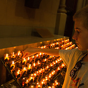 A young man lights a candle in memory of his grandmother at Saint Patricks cathedral in New York City.