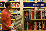 WH Smiths true crime and horror literature on sale in departures shopping area of Heathrow airport's Terminal 5.