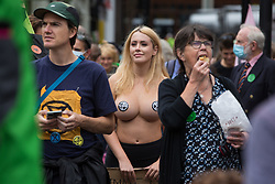 London, UK. 23rd August, 2021. A topless Extinction Rebellion activist takes part in the first day of Impossible Rebellion protests. Extinction Rebellion are calling on the UK government to cease all new fossil fuel investment with immediate effect. Credit: Mark Kerrison/Alamy Live News