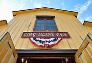 Old Bethpage, New York, USA. September 28, 2014. Above the Exhibition Hall entrance, patriotic red white and blue bunting decorates the Long Island Fair sign, at the 172nd Long Island Fair, a six-day fall county fair held late September and early October. A yearly event since 1842, the old-time festival is now held at a reconstructed fairground at Old Bethpage Village Restoration.