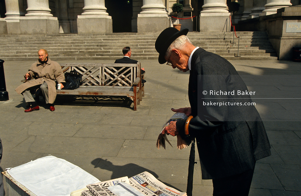 An elderly gentleman wearing a traditional bowler hat and carrying an umbrella, pauses to read the headlines in the London Evening Standard newspaper, before making his way home from Bank Triangle, outside the Bank of England. He is one of the last examples of a bygone age, when many in London's financial district wore such work clothes - a way of typifying a cretain breed of Englishness and class system, known all over, and still expected, around the world. Sadly, gents like this are very rare after modern fashions, lower standards and changed attitudes in the workplace meant that younger men no longer wanted to wear a stuffy outfit to work. The days of the bowler are fast disappearing.