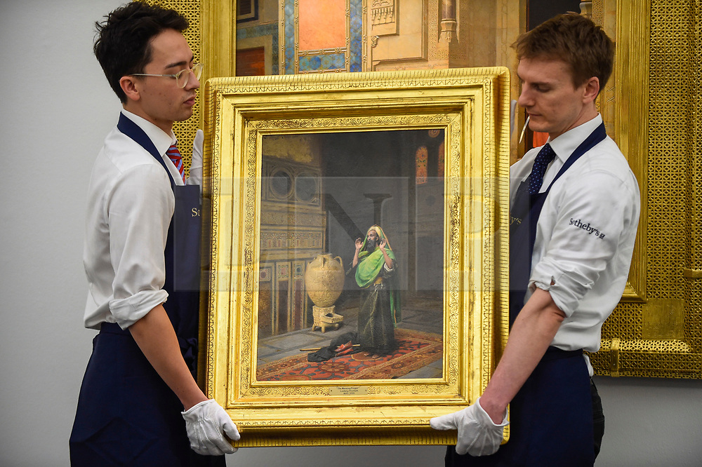 """© Licensed to London News Pictures. 11/10/2019. LONDON, UK. Technicians present """"The Morning Prayer"""", by Ludwig Deutsch, (Est GBP0.7-1.0m).  Preview of works from the Najd Collection of orientalist paintings at Sotheby's in New Bond Street, which record daily life in the historic Arab, Ottoman and Islamic worlds  All 155 paintings are on public view 11- 15 October, with 40 works to be auctioned on 22 October.  Photo credit: Stephen Chung/LNP"""