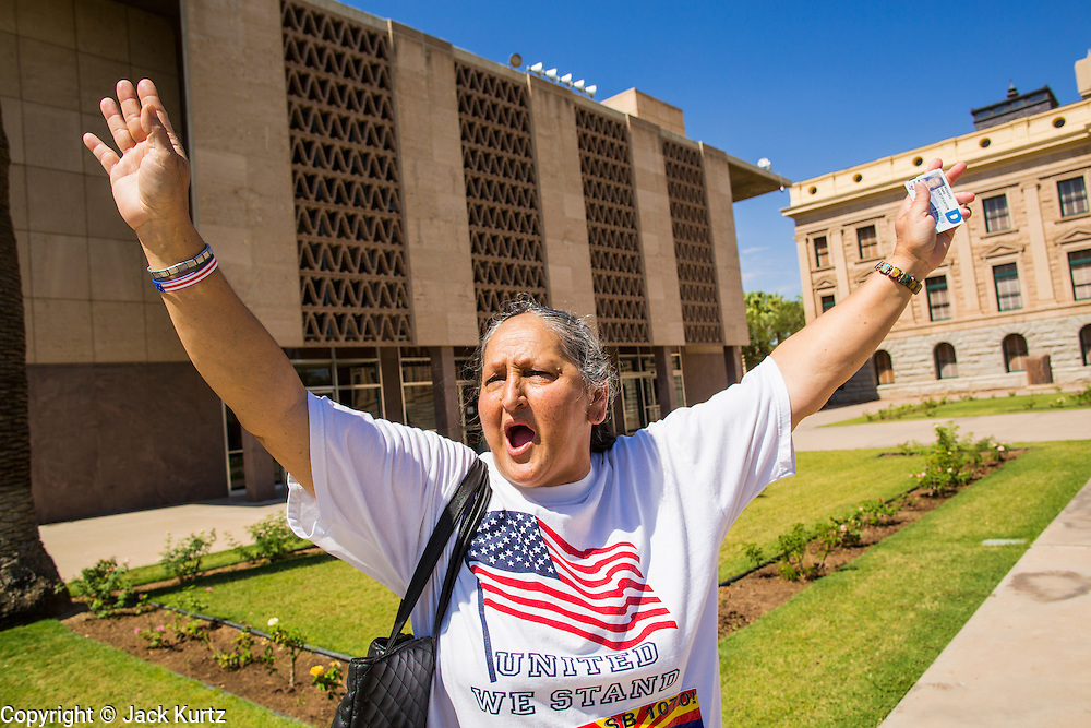 25 JUNE 2012 - PHOENIX, AZ:   MARTHA PAYAN (left) celebrates in front of the Arizona state capitol after the US Supreme Court overturned most of SB1070 Monday. Many conservatives in Arizona viewed the Court's decision as a victory because it let stand one small portion of the law. The case, US v. Arizona, determined whether or not Arizona's tough anti-immigration law, popularly known as SB1070 was constitutional. The court struck down most of the law but left one section standing, the section authorizing local police agencies to check the immigration status of people they come into contact with.     PHOTO BY JACK KURTZ