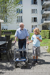 Grandfather with grandson walking in garden, Bavaria, Germany
