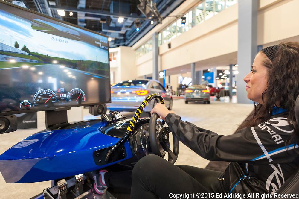 MIAMI BEACH, FL, USA - NOVEMBER 6, 2015: Spokes model driving the Hyundai racing simulator during the 2015 Miami International Auto Show at the Miami Beach Convention Center in downtown Miami Beach.