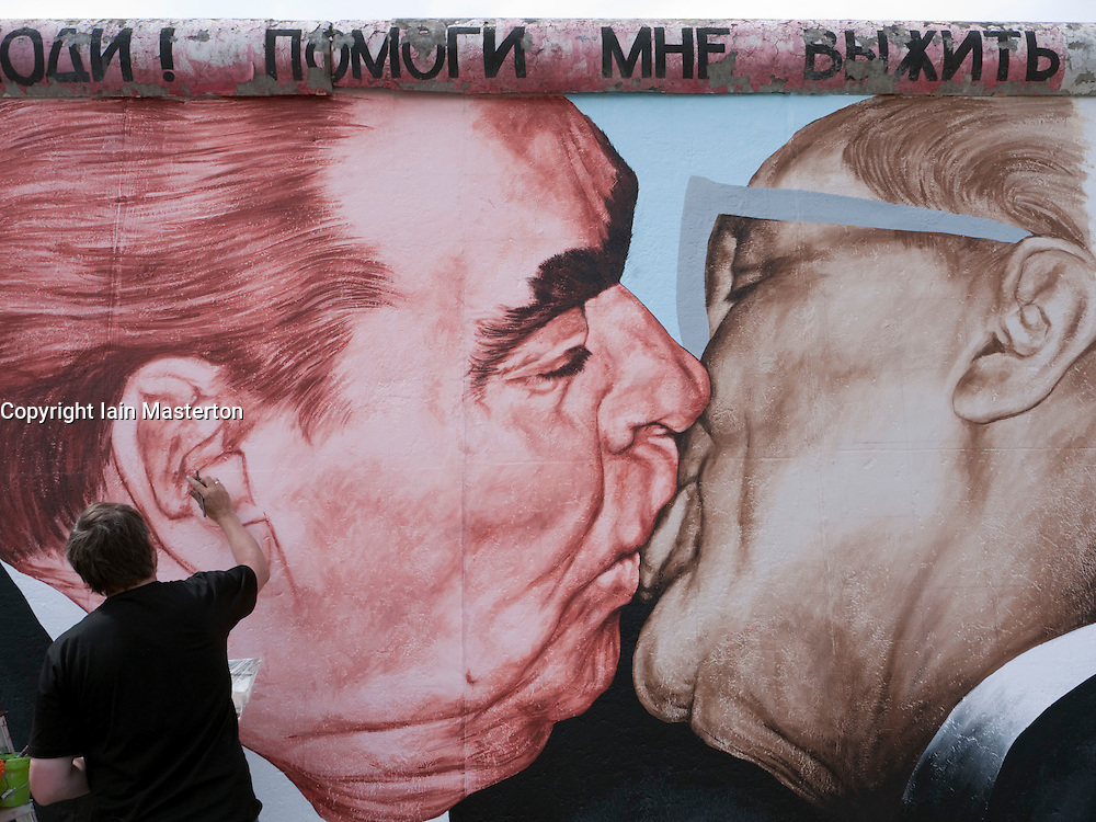 Russian artist Dimitry Vrubel repainting his famous  original mural of Brezhnev kissing Honecker on the Berlin Wall at the East Side Gallery in Berlin