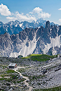 """The peaks of the Cadini Group jut high above Rifugio Lavaredo in the Dolomites, near Cortina d'Ampezzo, Italy, Europe. In the Cadini di Misurina, Cima Grande rises to 2999 meters (9839 feet), between Cima Piccola and Cima Ovest. Hike for spectacular views around Tre Cime di Lavaredo (Italian for """"Three Peaks of Lavaredo,"""" or in German called Drei Zinnen, """"Three Merlons""""). The Dolomites are part of the Southern Limestone Alps, in northern Italy, Europe. UNESCO honored the Dolomites as a natural World Heritage Site in 2009."""