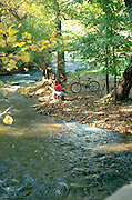 Bicyclist age 56 reading by Minnehaha creek as it flows through Minnehaha Park.  Minneapolis  Minnesota USA