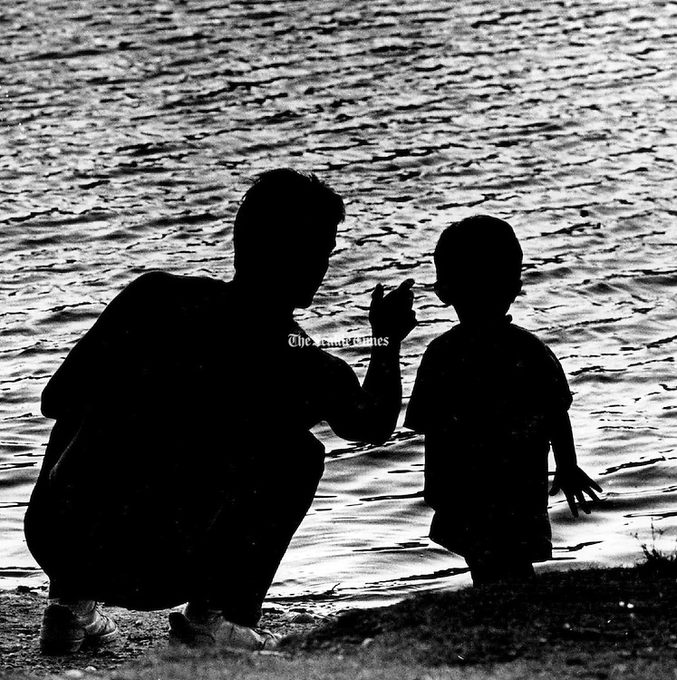 And watch the ripples: A father teaches his two-year-old son, the finer points of skipping stones at Five-Mile Lake Park in Federal Way. (Mike Levy / The Seattle Times, 1988)