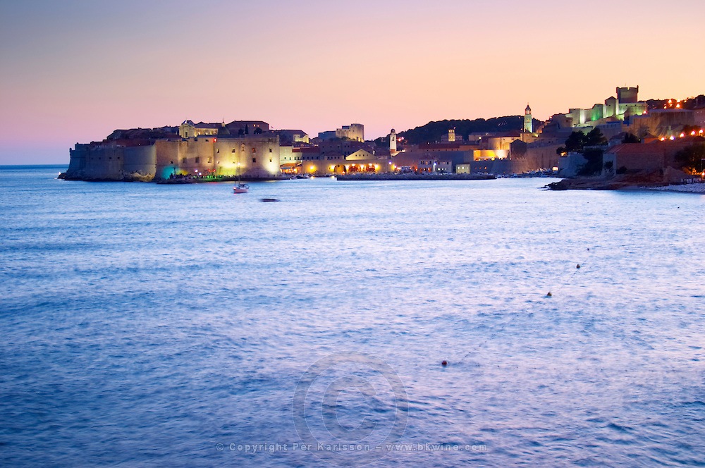 View over the Old Town in the evening after sunset, the city lights glimmering, the sky deep blue and orange pink, deep blue sea from the luxury Excelsior Hotel and Spa restaurant terrace Dubrovnik, old city. Dalmatian Coast, Croatia, Europe.