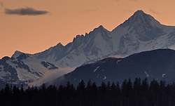 Mount LaPerouse and other peaks of the Fairweather Range basks in the light from a late evening sunset in Glacier Bay National Park and Preserve in this view seen from Glacier Bay Lodge located in Bartlett Cove of the park in southeast Alaska.