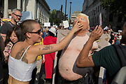 Protesters against the visit of US President Donald Trump to the UK, punch an effigy of Trump in Trafalgar Square after marching through central London, on 13th July 2018, in London, England.
