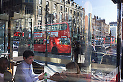 Lunchtime diners in a Pret-a-Manger restaurant in Clerkenwell. with city pedestriand and a red London bus.