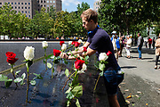 New York, NY - 10 September 2021. Official and private memorials are held at the 9/11 memorial site on the day before the 20th anniversary of the World Trade Center attacks. A worker places roses in the names of some of those lost.