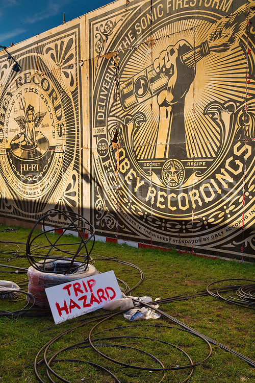 Glastonbury Festival, 2015. Shangri La is a festival of contemporary performing arts held each year within Glastonbury Festival. The theme for the 2015 Shangri La was Protest.  Getting the Shangri La Hell stage prepared with OBEY posters by Shepard Fairey, with a risk warning - Trip Hazard - showing