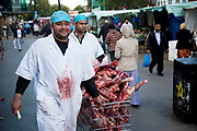 Butchers push carcasses of meat (lamb) along the market on Whitechapel High Street in East London. This area in the Tower Hamlets is predominantly Muslim with just over 50% from Bangladeshi descent. This is known as a very poor area of London's East End.