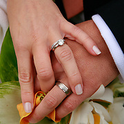 A Bride and Groom intertwine their fingers with their new wedding bands exposed to the camera.