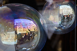 London, UK. 2 July, 2019.  Relections of climate change activists from Extinction Rebellion Art and Culture taking part in a silent procession visiting the offices of five major oil companies - ENI, CNPC, Saudi Aramco, Repsol and BP - to declare them a crime scene appear in a bauble in a shop window.