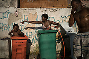 In this Sept. 11, 2017 photo, a woman and youth use tall trash containers to shower outside their squatter building that used to house the Brazilian Institute of Geography and Statistics (IBGE) in the Mangueira slum of Rio de Janeiro, Brazil. The World Bank estimates that between the start of 2016 and the end of this year, 2.5 million to 3.6 million Brazilians will have fallen back below the poverty line of 140 Brazilian reais per month, about $44 at current exchange rates. (AP Photo/Felipe Dana)